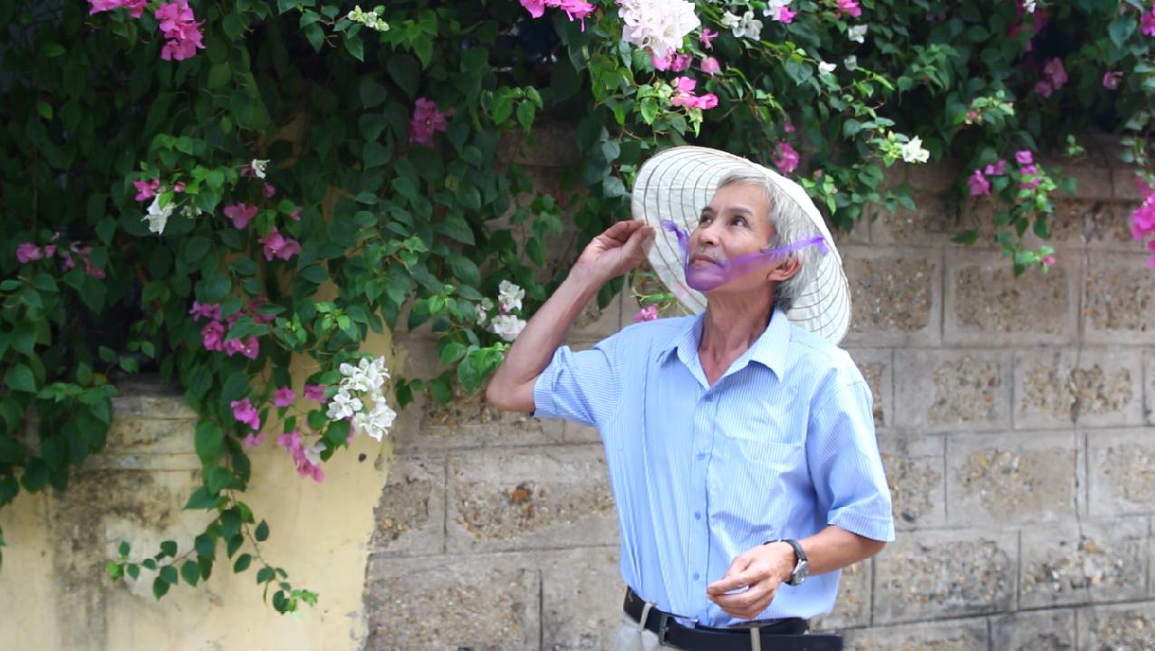 """Ông Hùng cũng rất """"điệu đà"""" tạo dáng cùng chiếc nón bên giàn hoa giấy trước nhà. Ảnh: NL."""